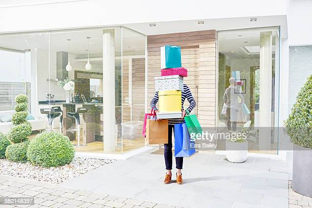 woman hidden by her shopping bags and boxes - consumerism stock pictures, royalty-free photos & images