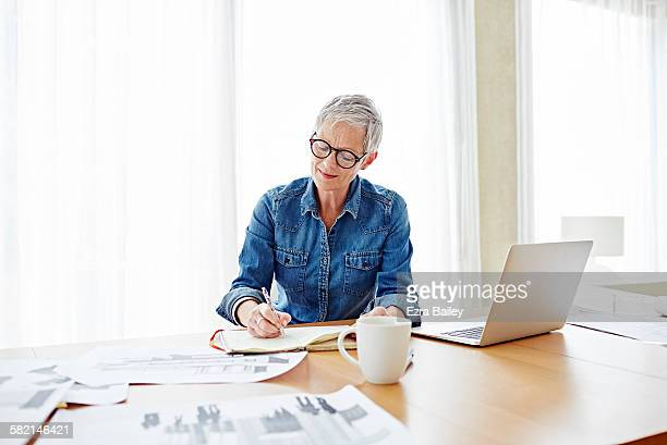 modern mature businesswoman working at her desk - businesswoman stock pictures, royalty-free photos & images