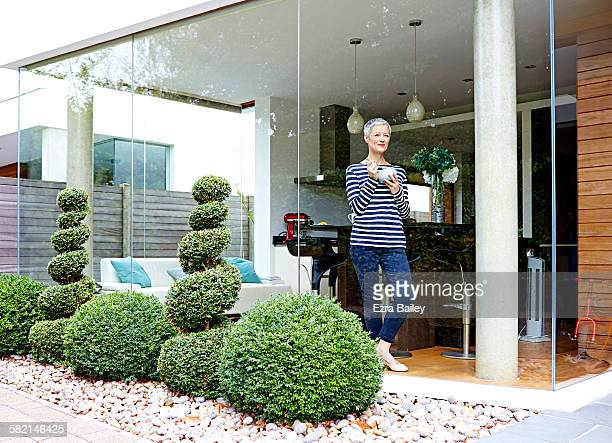 woman relaxes as she looks out of her apartment - serene people stock pictures, royalty-free photos & images