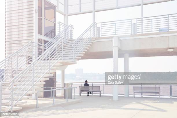 businessman enjoying the view over the river - parapetto barriera foto e immagini stock