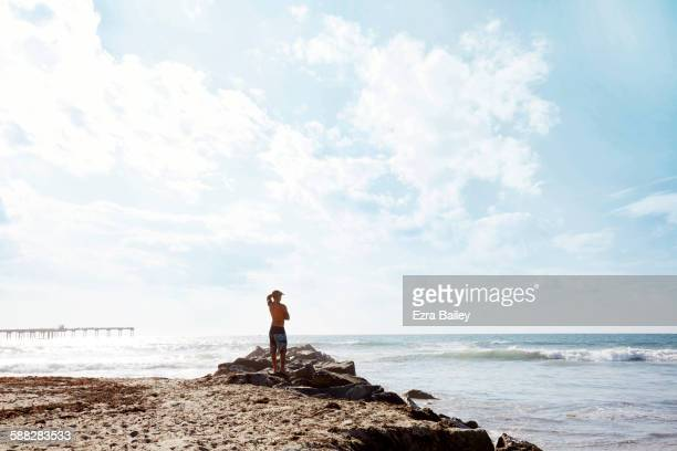 Man looking out to sea in the sun.