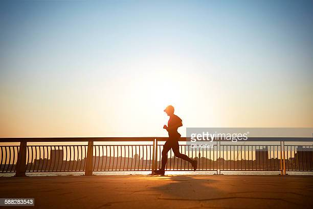 man enjoying an early morning jog in the city. - morning stockfoto's en -beelden