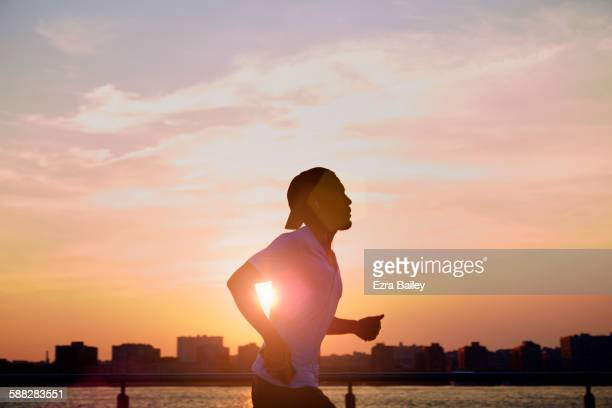 man enjoying an early morning jog in the city. - ochtend stockfoto's en -beelden