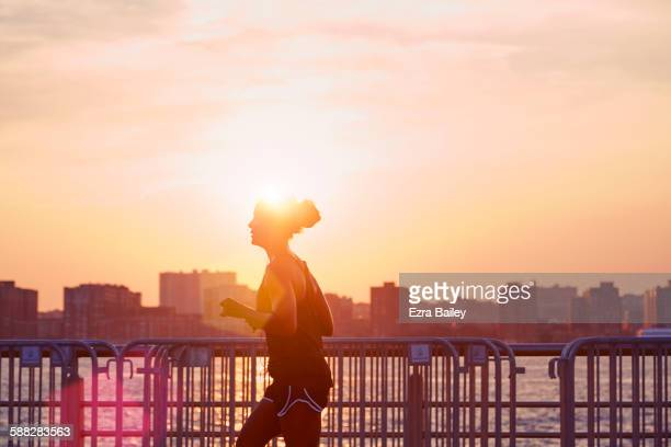 woman going for an early morning jog in the city. - center athlete stock pictures, royalty-free photos & images