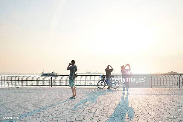 People taking selfies at sunset in Manhattan,