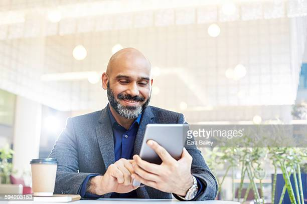 modern businessman using his tablet in an office. - satisfaction stock pictures, royalty-free photos & images