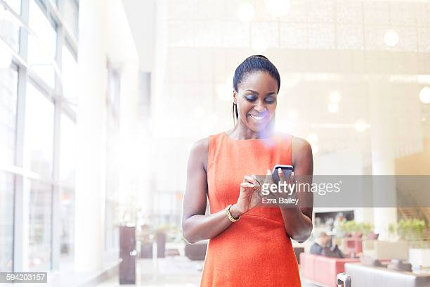 businesswoman in modern office checking her phone. - black hair stock pictures, royalty-free photos & images