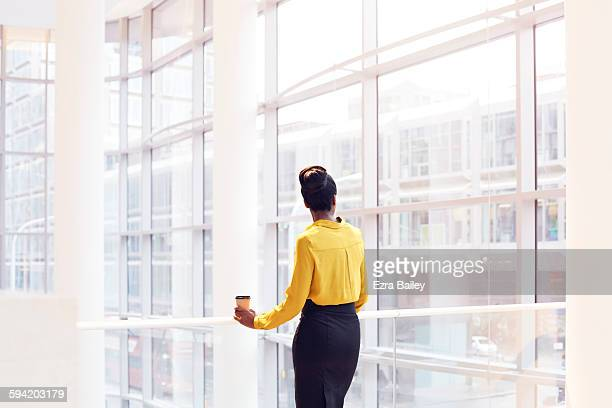 modern business woman looking out the window. - yellow stock pictures, royalty-free photos & images