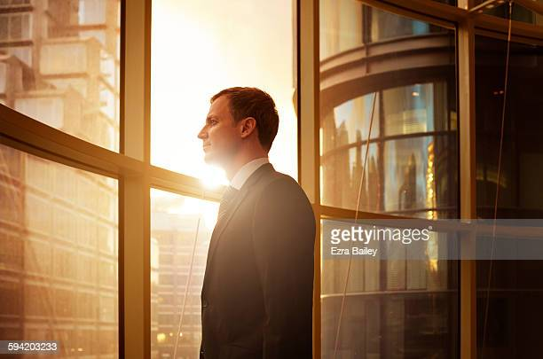 Businessman looking out over the city at sunrise.