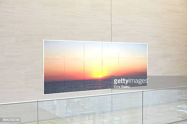 A sunset printed on paper stuck on an office wall