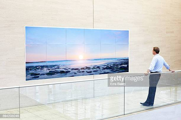 businessman admires a sunset printed on paper. - tranquil scene foto e immagini stock