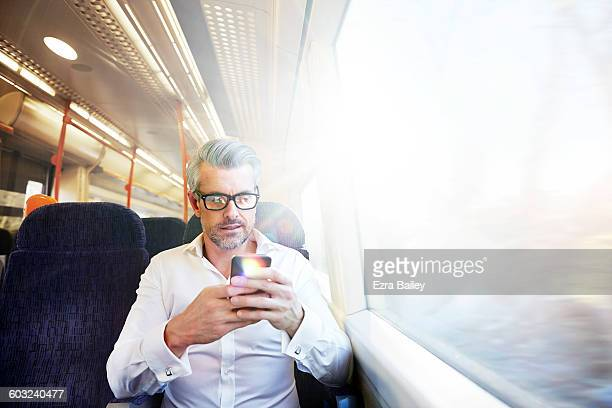 Businessman writing emails on a commuter train.