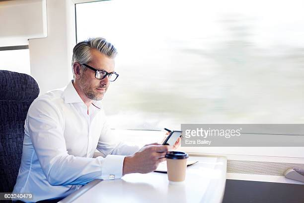 Businessman checking his phone on the train.
