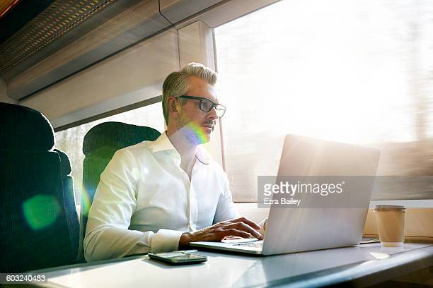 businessman working on a laptop on a train. - reflexo de luz efeito fotográfico - fotografias e filmes do acervo