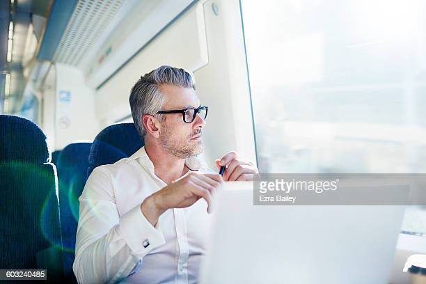 businessman brainstorming while on a train. - image focus technique stock pictures, royalty-free photos & images