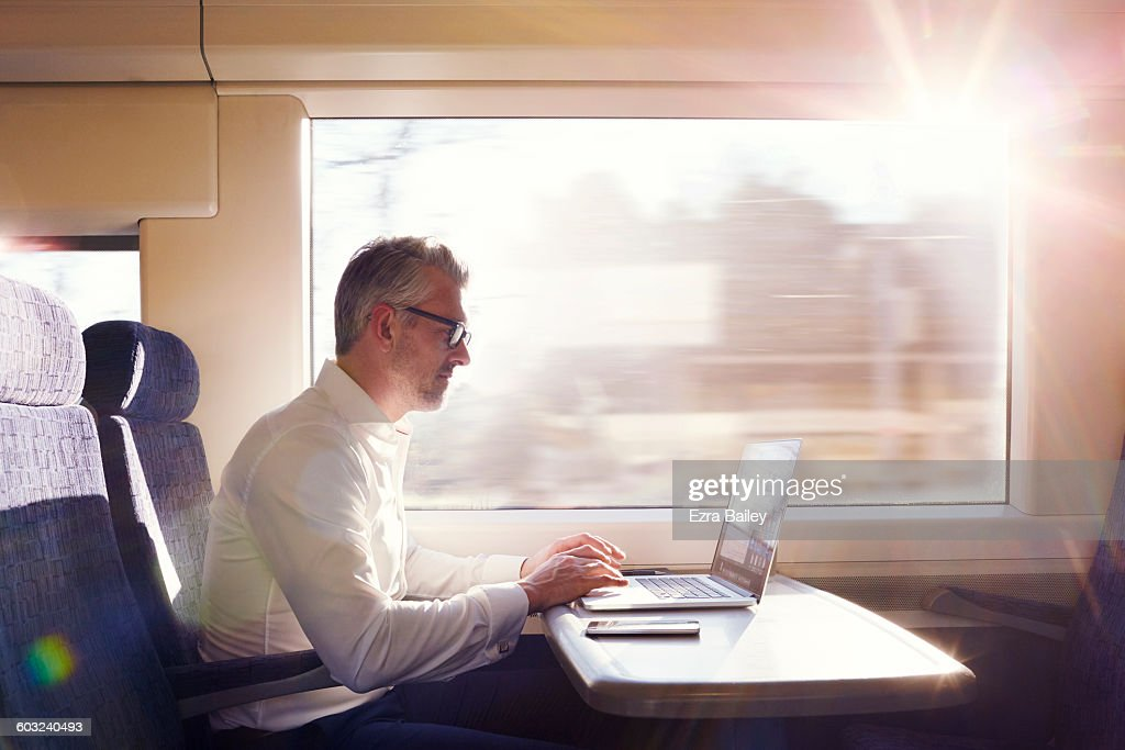 Businessman working on a commuter train. : Stock Photo