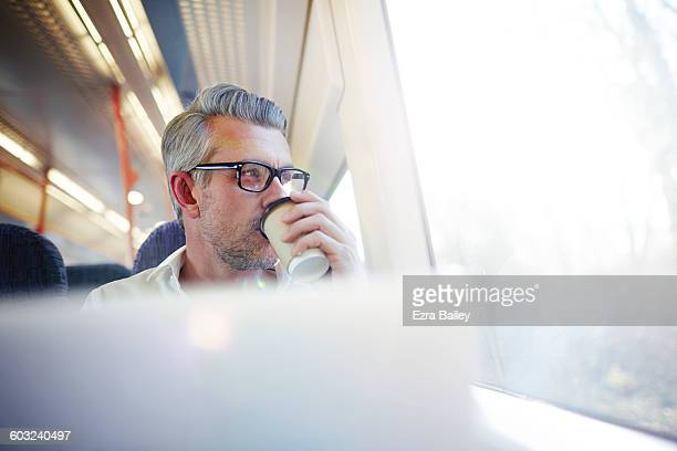 Businessman on a commuter train drinking coffee.