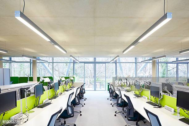 modern open plan office with hot desks. - hot desking stock pictures, royalty-free photos & images