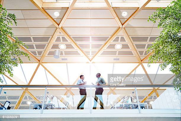 work colleagues having a catch up in modern office - built structure stock pictures, royalty-free photos & images