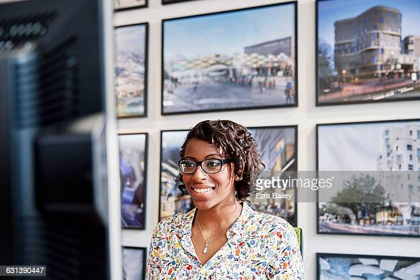 creative employee working at her desk smiling. - vanguardians stock pictures, royalty-free photos & images