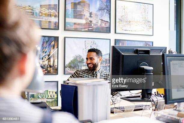 Creative employee at desk chatting with coworkers.