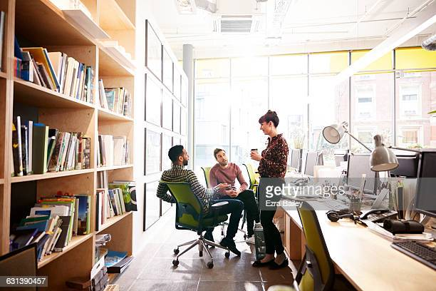 coworkers chat informally over coffee at desk - three people stock pictures, royalty-free photos & images