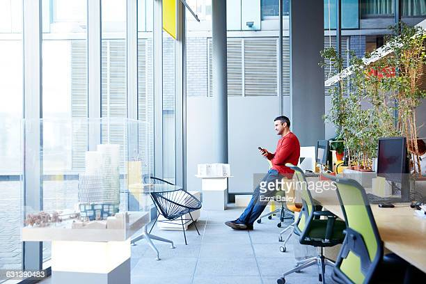 Designer relaxing and looking out of window.