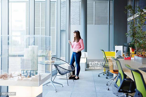 creative girl looking out of window holding phone - one young woman only stock pictures, royalty-free photos & images