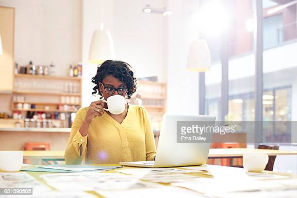 creative woman working at desk with coffee - achter stockfoto's en -beelden