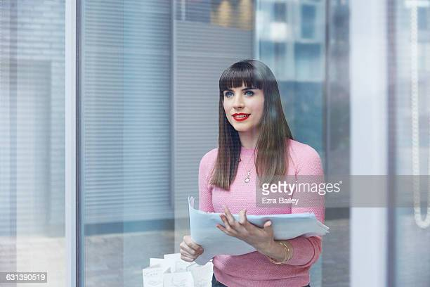 Creative woman holding plans looking out of window