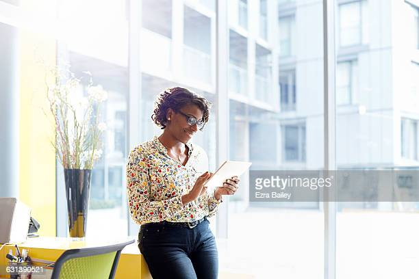 smiling businesswoman works on tablet in sunlight - frau bluse durchsichtig stock-fotos und bilder
