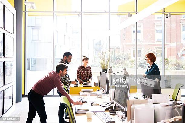 Coworkers talking over ideas in open plan office