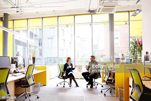 coworkers chatting with coffee discussing projects - business casual stock pictures, royalty-free photos & images