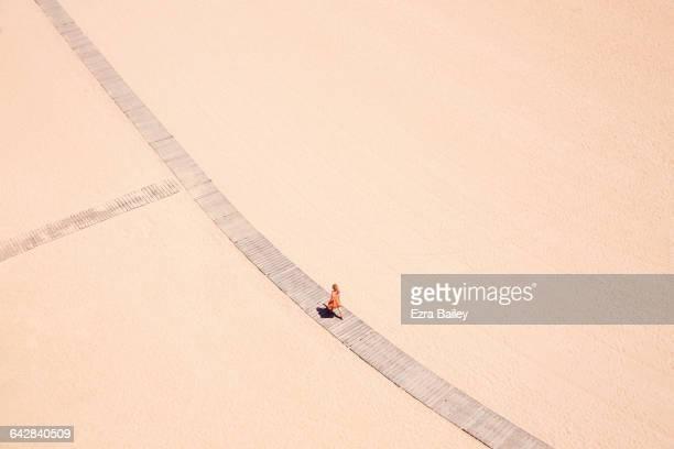 woman in orange walks along beach boardwalk - stile minimalista foto e immagini stock