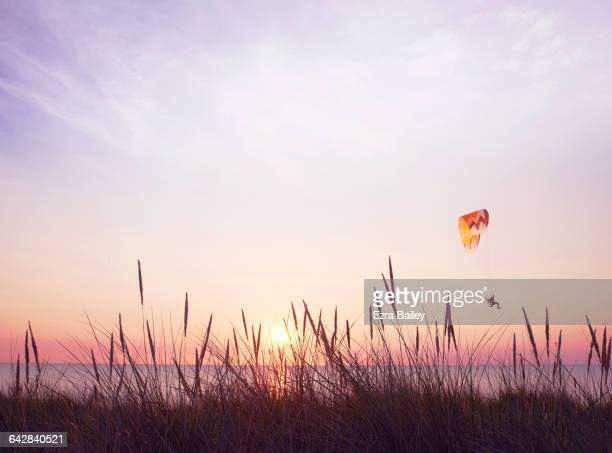 Paraglider over sea at sunset