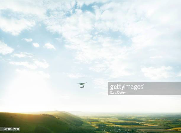 Hang glider above green hills in cloudy blue sky
