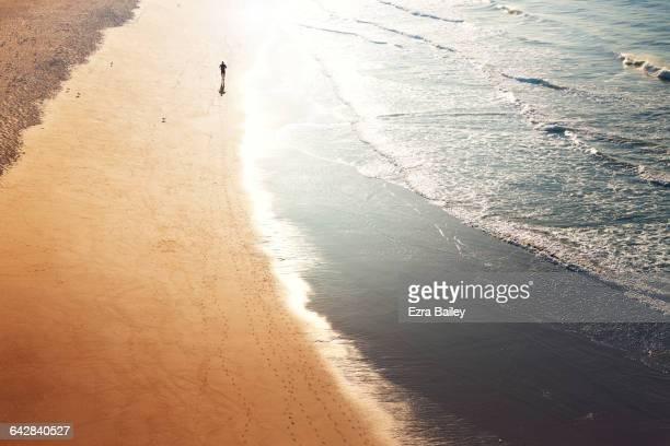 A runner jogging along the shoreline at sunrise