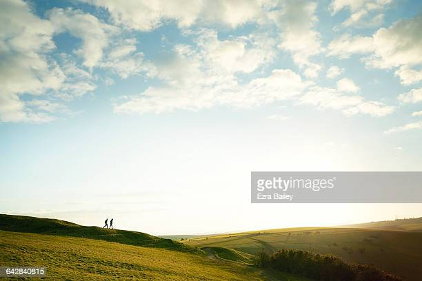 silhouette of couple walking on hilltop - two people stock pictures, royalty-free photos & images
