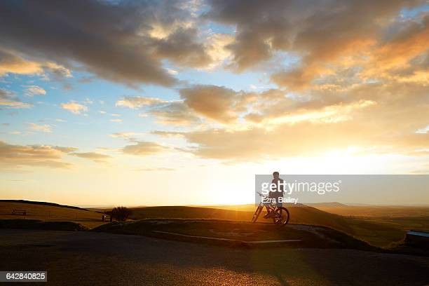 mountain biker admiring the view from hilltop - sunrise dawn stock pictures, royalty-free photos & images