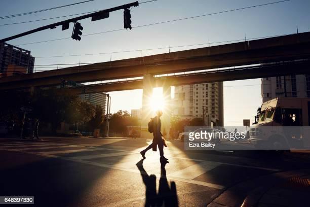 man crossing road at sunset in miami - pedone ruolo dell'uomo foto e immagini stock