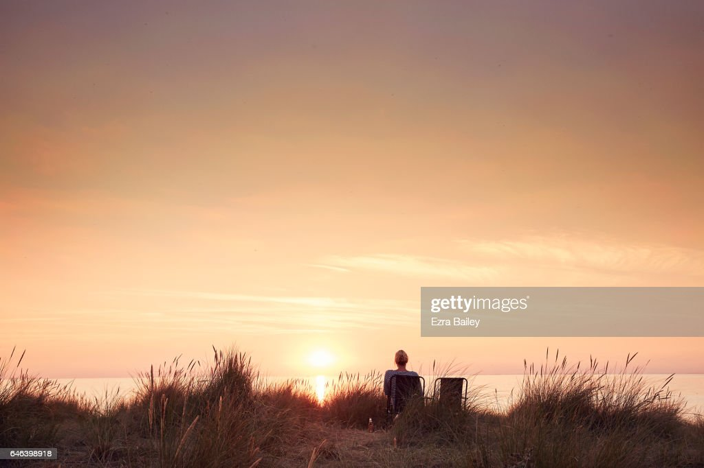 Woman watching the sun set : Stock Photo
