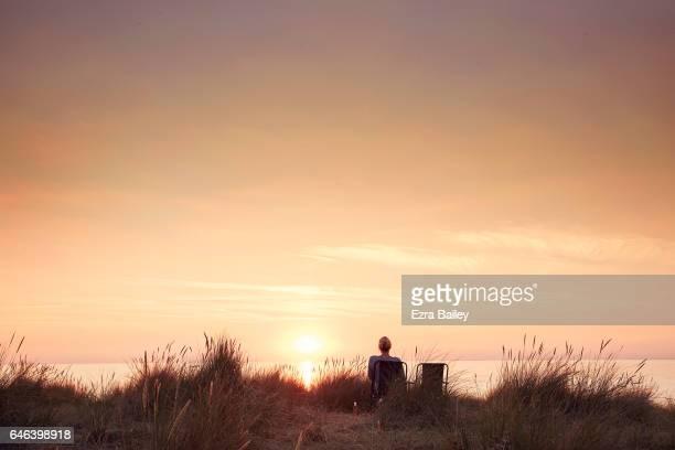 woman watching the sun set - belleza de la naturaleza fotografías e imágenes de stock
