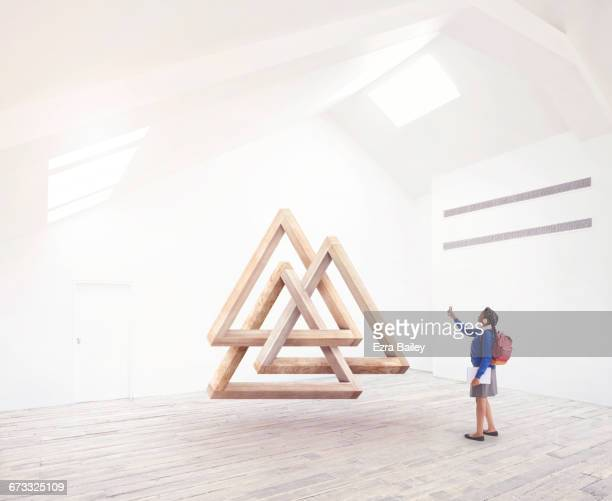 School girl taking a photo of Impossible triangles