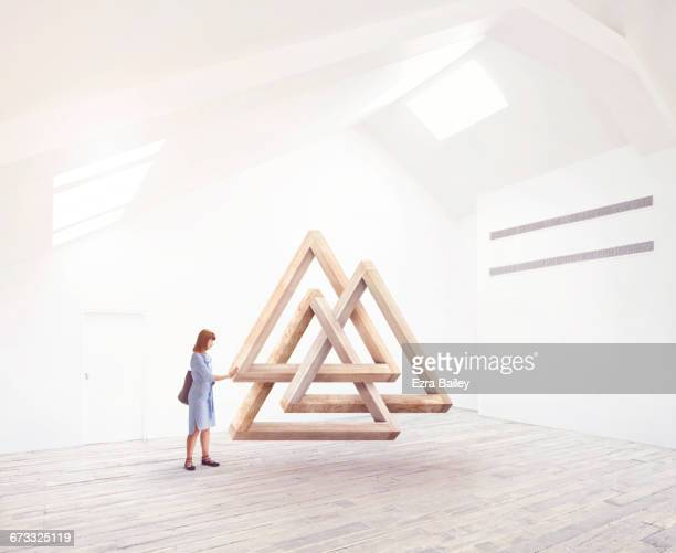 Woman being inspired by an impossible triangle.