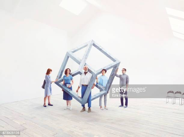 People interacting with an impossible cube.