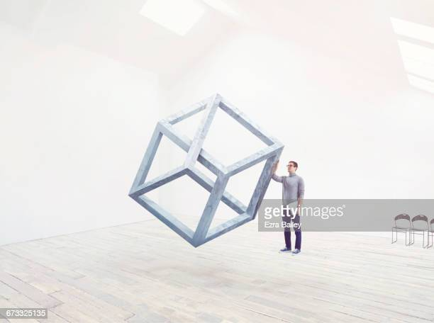 designer being inspired by an impossible cube. - thinking outside the box englische redewendung stock-fotos und bilder