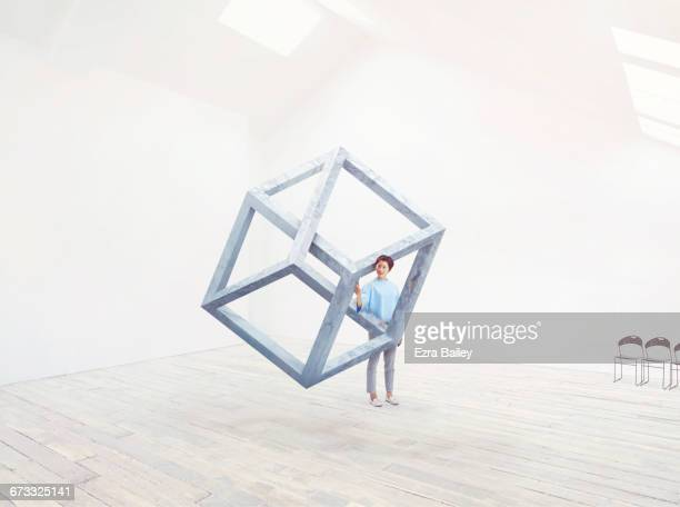 woman interacting with an impossible cube. - thinking outside the box englische redewendung stock-fotos und bilder