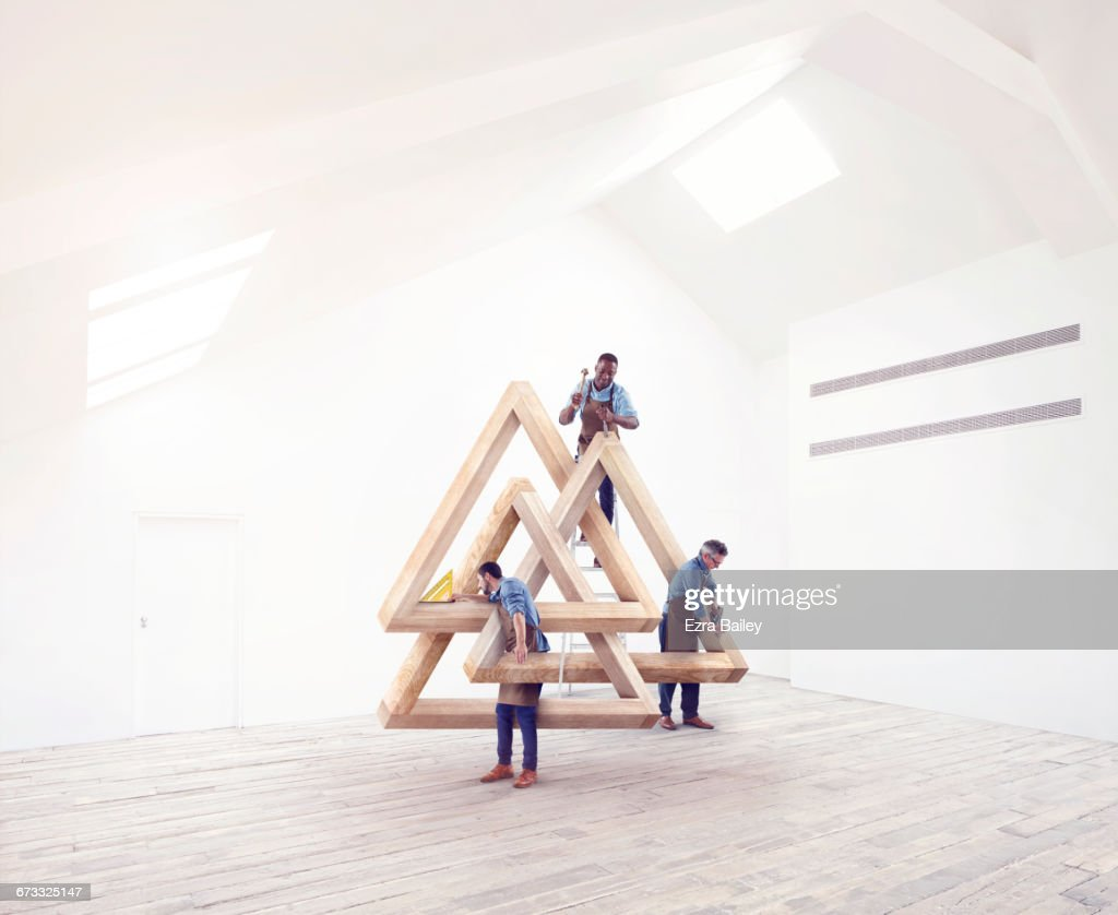 Designers working on an impossible triangle. : Stock Photo