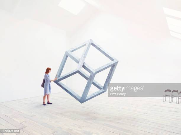 woman being inspired by an impossible shape. - thinking outside the box englische redewendung stock-fotos und bilder