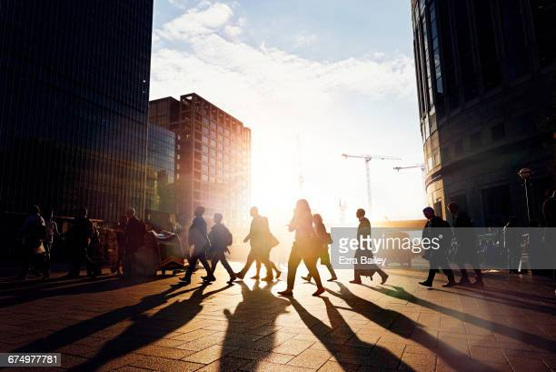 Employees walking to work in the city at sunrise